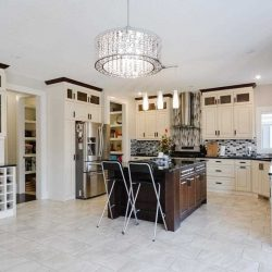Kitchen with white ceiling, floor, walls and cabinets; dark wood island with steel/plastic stools; large chandelier overhead