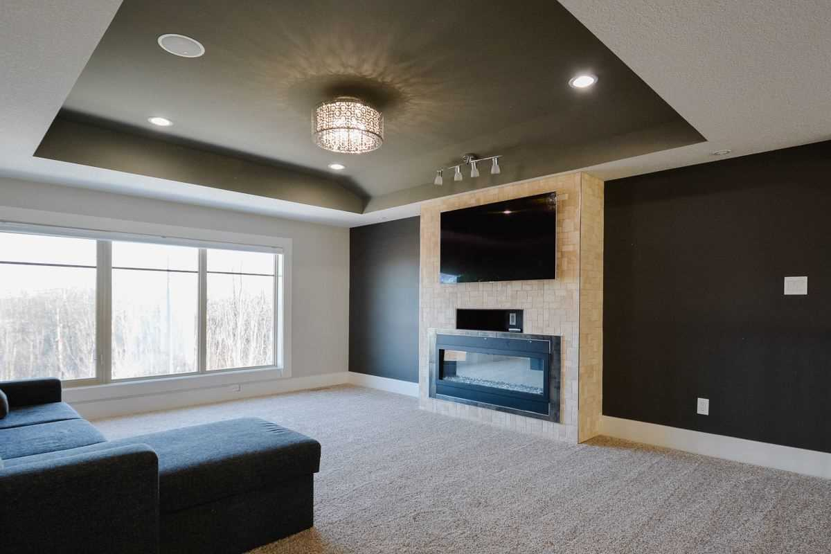 Upstairs TV room with light carpet, black, white and beige-stone walls; recessed ceiling with chandelier; dark sectional couch