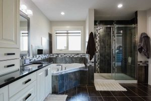 En suite bathroom with white walls and cabinets, black tile floor; window above corner tub, next two large shower