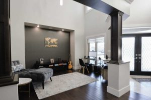 Interior home entrance, white walls with dark wood floor, doors and finishes; white rug, grey chaise lounge, acoustic guitar