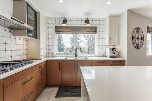 White backsplash tiles brighten the kitchen.