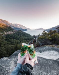two people drinking while looking out at mountains
