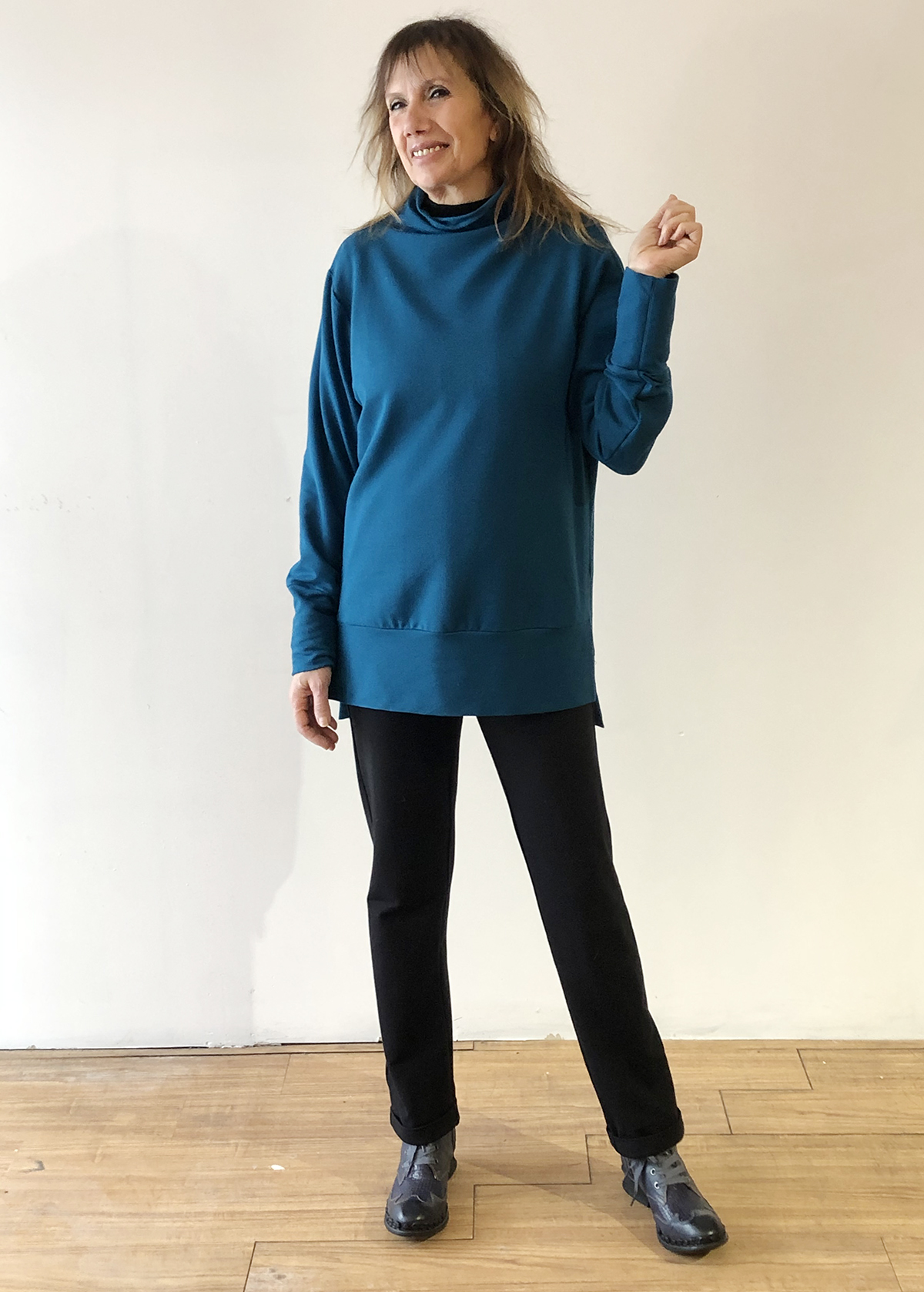 The model is wearing a sweater that goes past her hips, in Moroccan blue