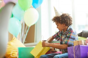 Young boy opening gifts at a birthday party