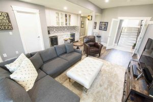 Basement with white walls, grey couch, wet bar in the background.