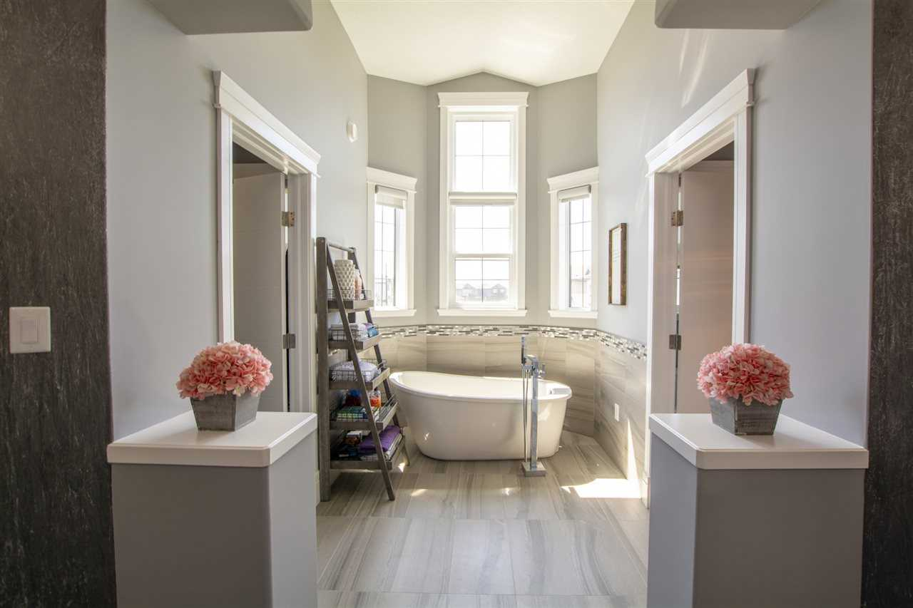 Freestanding soaker tub in a window cove next to shelving; fake flowers on pedestals in foreground