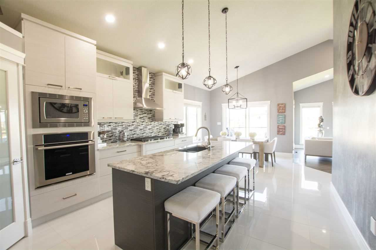 Kitchen: white walls, floor, island and stools; three hanging lights over island