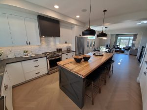 Black kitchen island with wood counter and black stools. White walls and cabinets.