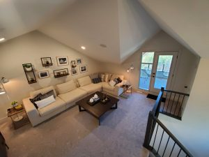 Grey carpet, white sectional couch, angled ceiling, patio.
