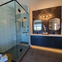 Large glass shower, dark tile floor, black cabinets, double sinks.