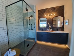 Large glass shower, dark tile floor, black cabinets, double sinks.
