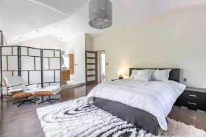 Master suite with grey hardwood floor and white walls; a grey circular chandelier hangs mid-room over the grey bed with white duvet to the right, on top of black and white shag carpet; a light wood and white chair and foot stool sit left, in front of white-with-black lines room divider, sectioning off the en suite
