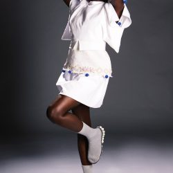 Model: Nyagoa (kicking), dressed all in white, designs by Noah Milo