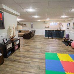 Basement with white walls and false ceiling, hardwood floor; multi-coloured floor mat, dark shelving, navy bar, dark brown couch