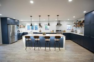 Kitchen with white ceiling and walls, light panel flooring, navy cabinets and white quartz waterfall island