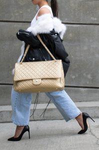 Business_WomanWalking_BigGoldChanelBackOverArm_Jeans_HighBlackShoes