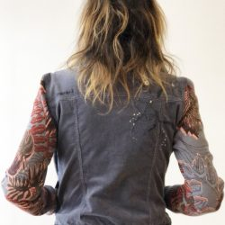 The denim jacket has sleeves decorated with red designs