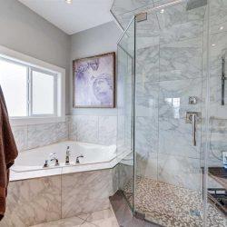 Marble en suite bathroom; large glass shower next to embedded tub under window