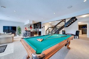 Basement with white walls and light carpet; green-surface pool table in foreground; dark-cabinet bar, fake plant, large TV and light beige couch to the left