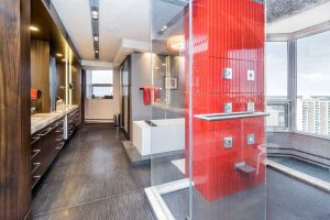En suite with dark grey, white-lined tile floor; wood cabinetry on left; glass shower with bright red wall and grey tile floor on right, looking out to city view