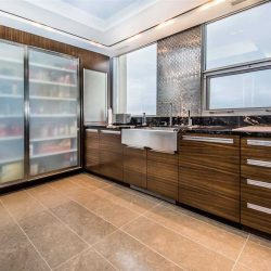Interior kitchen with beige tile floor; black-with-white-splattered marble counter, steel backsplash in between frosted windows, above wood cabinets; frosted glass pantry doors on left