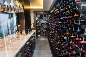 Wine room with grey tile floor; beige counter bar on left with decanters and steel chandelier on left; giant wall of wine on right