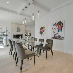 Interior home, dining foreground/living area background; white oak floor, white walls and coffered ceiling with five hanging lights over glass dining table with grey chairs; two black and white paintings of a woman's face with coloured flowers and butterflies in her hair