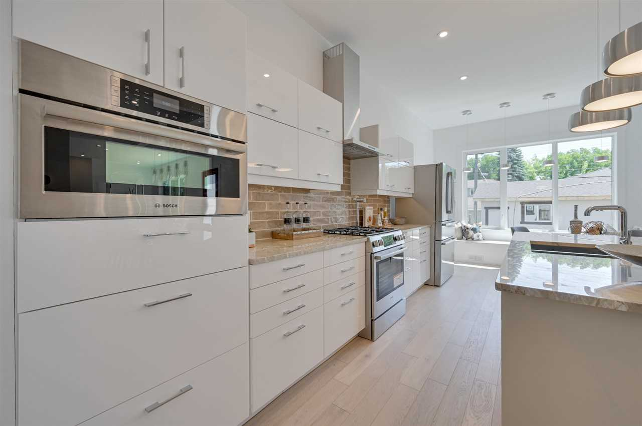 Kitchen with white oak floor, white cabinets and walls, brick backsplash, microwave; three hanging lights over white island with sink