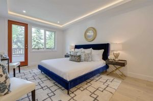 Mater bedroom with white ceiling and walls, white oak floor; track lighting around ceiling perimeter; blue bed frame with white sheets; wood-framed glass door leading to balcony