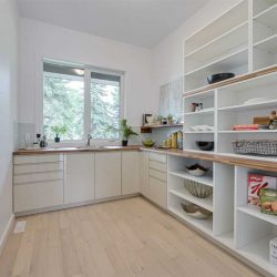 Butler pantry with large windows, sink and floor-to-ceiling shelves. White walls and white oak floor