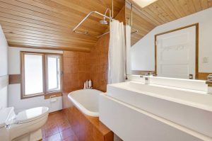 Wood floor, ceiling and walls; white sinks, toilet and tub with free-hanging curtain.