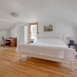 Wood floor, white walls, white bed, a window on each of three walls.