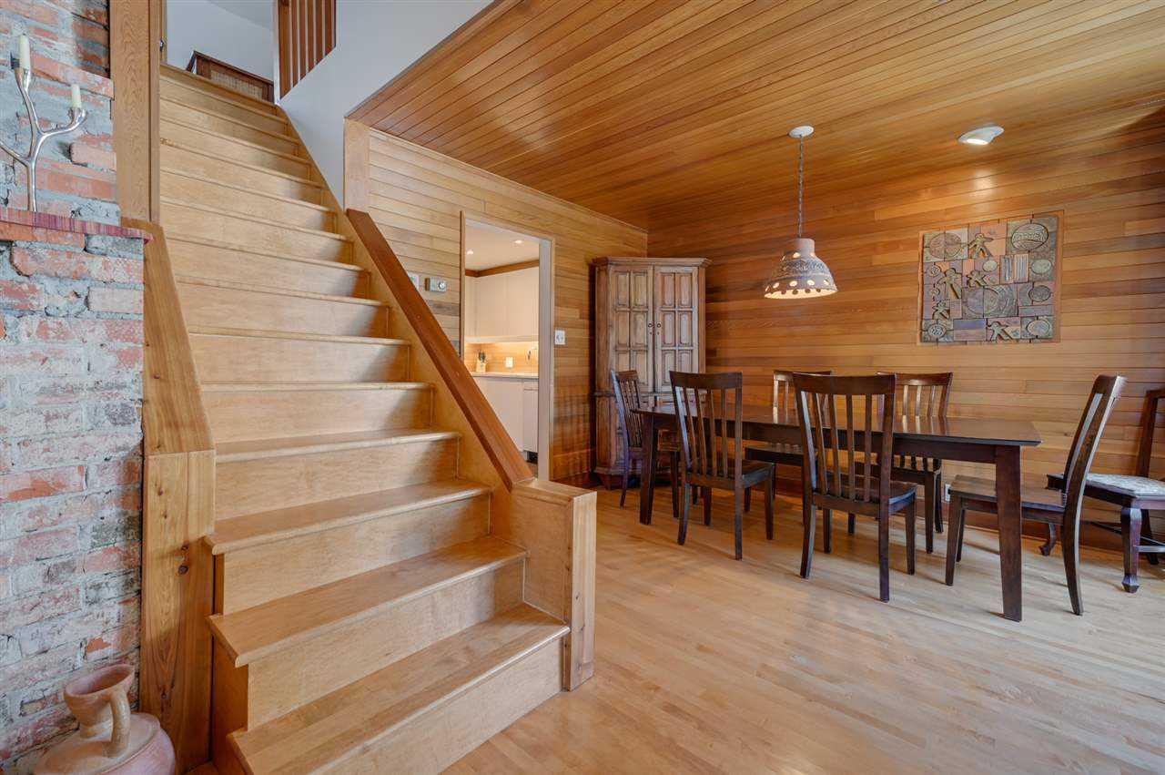 Wood stairs, wood ceiling, wood floor; slightly darker wood furniture.