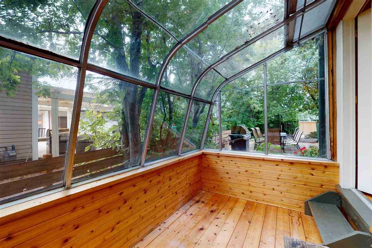 Sunroom with wood floor, looking out to trees and a barbecue.