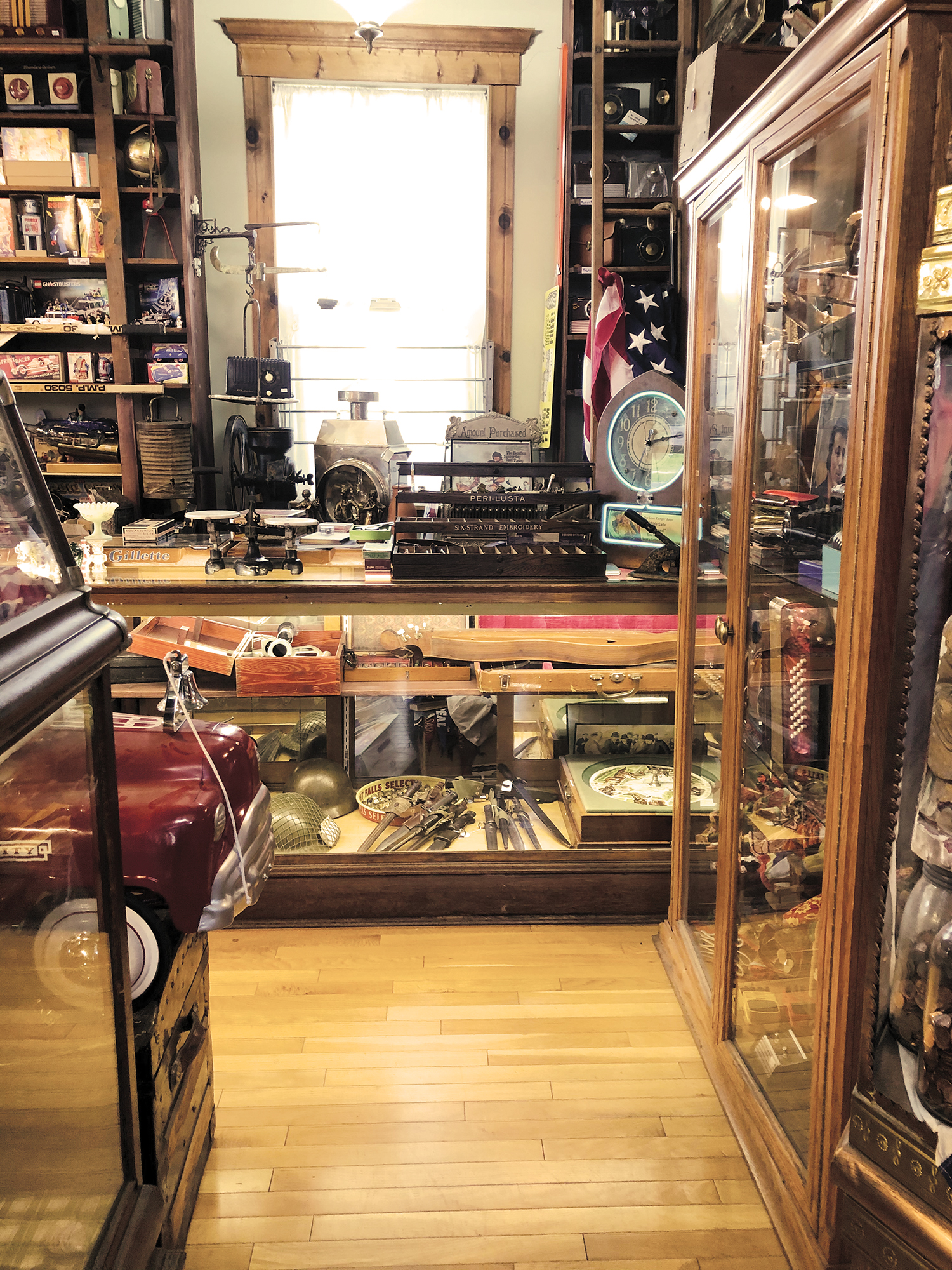Antique store, wood floor, glass case and cabinet, wood framed window, front end of dark red model car.