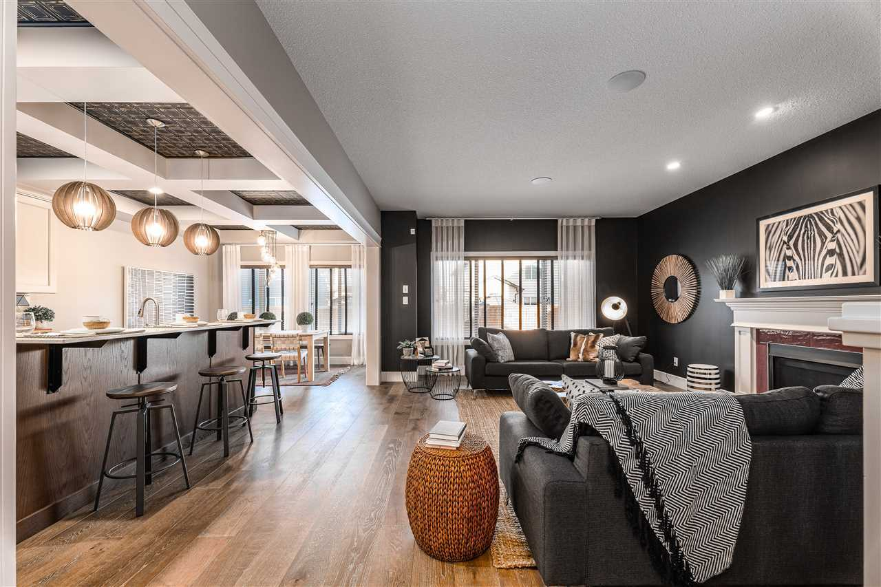Interior living room/kitchen; hardwood floor, white ceiling; black living room wall with dark grey couches, white fireplace mantle; white ceiling beam separating living room and kitchen; dark wood kitchen island with three stools