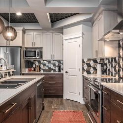 Kitchen with black pattern in between coffered ceiling; white counters, cupboards and pantry door; dark wood drawers; red mat on the floor; three lights hanging over the island