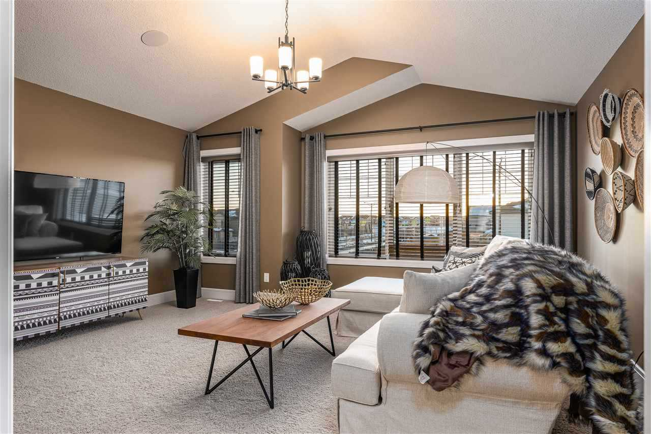 Upstairs bonus room with peaked ceiling and large windows and grey curtains; light grey carpet, white couch with black and white animal pattern blanket; wood coffee table