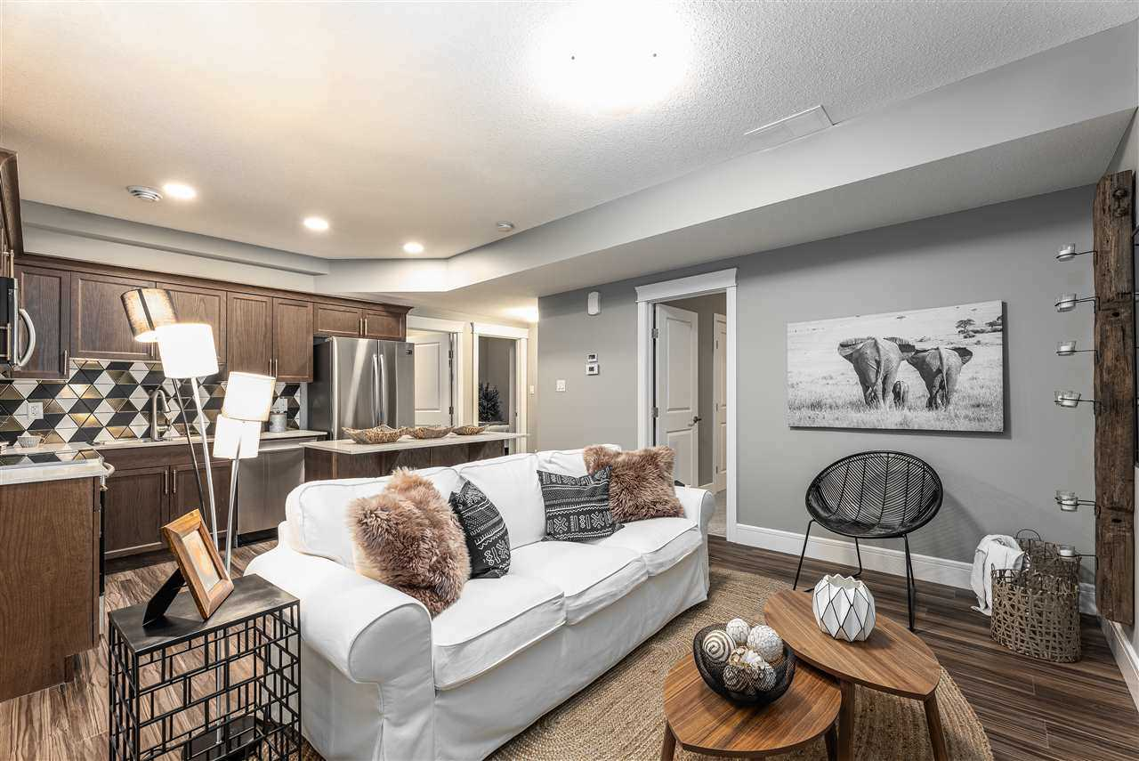 Basement suite with white ceiling and walls, hardwood floor; white couch, small wood coffee tables; wood cupboards in kitchen, triangle pattern backsplash