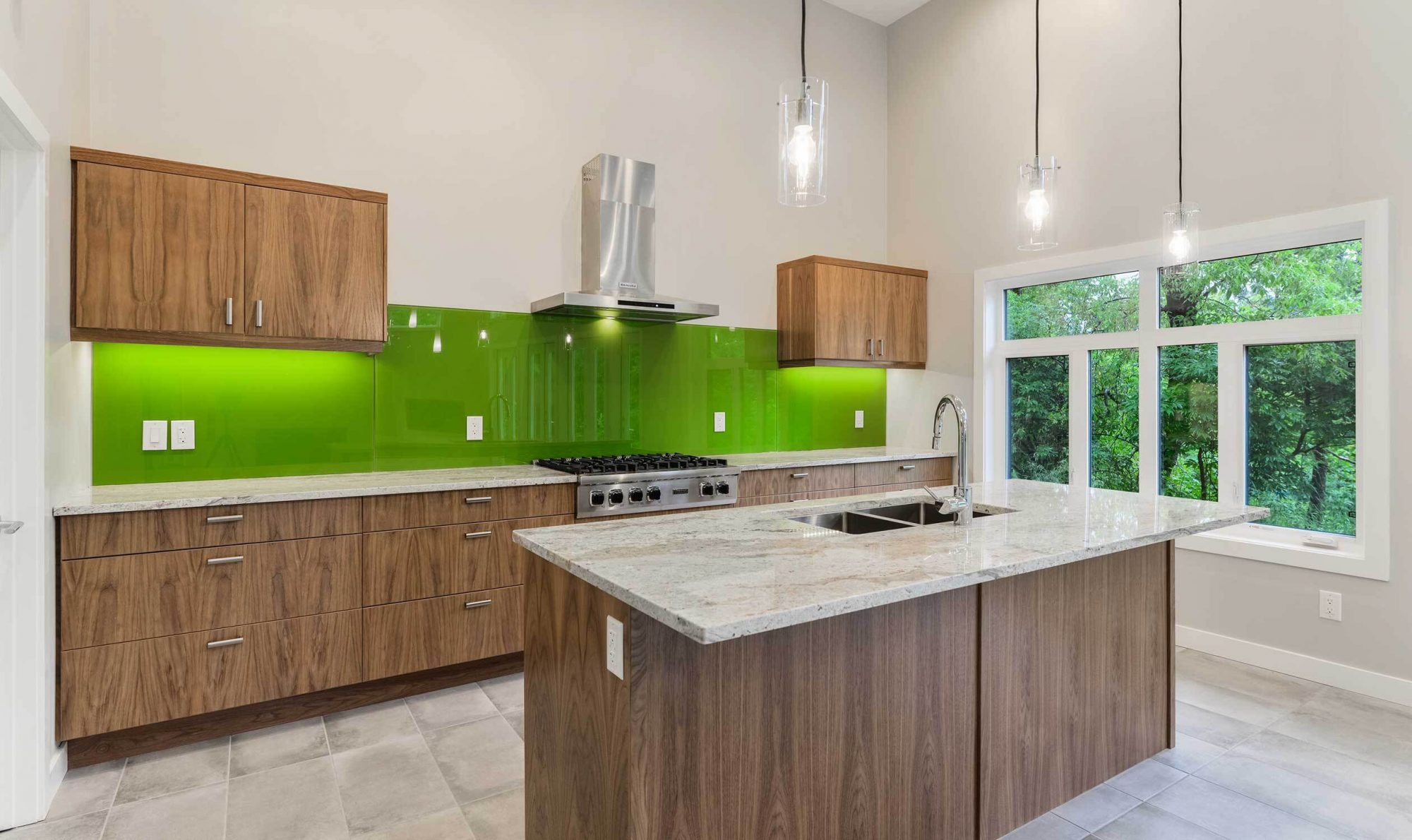 Open, kitchen with beautiful green backsplash and large windows
