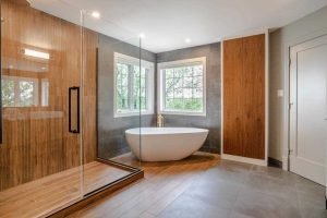 En suite bathroom with white ceiling, tile floor on right, wood floor on left leading to glass-wall shower lined with wood; white soaker tub in windowed corner