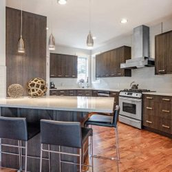 Kitchen with hardwood floor, white ceiling and walls, dark wood cabinets and grey counters; island in foreground with four black stools