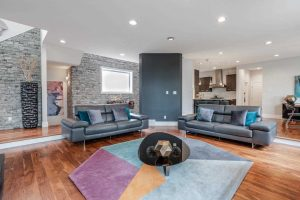 Living room, hardwood floor, white ceiling and walls; octagon, pastel coloured carpet under black glass coffee table; light grey couches on either side; grey stone wall to the left, kitchen in background