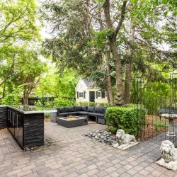 Backyard ground floor patio made of grey stone; wrought iron gate to right, black stone outdoor kitchen to left, black sectional patio couch with square fire pit in middle; shed that looks like a tiny guest house in background