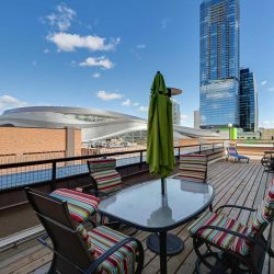 Exterior deck view of Rogers Place; glass table with green umbrella and rainbow coloured chair cushions; skyscrapers in background to right