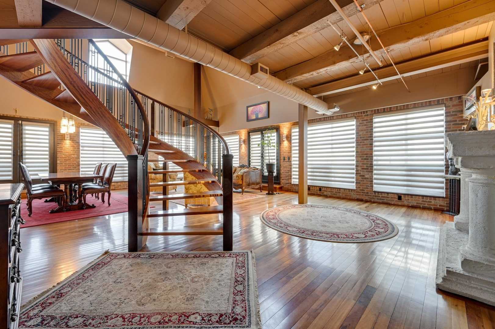 Interior condo entrance, tiger wood floor, brick walls and beige open ceiling; large windows along walls; area rug in front of circular staircase on right; white fireplace mantle on left