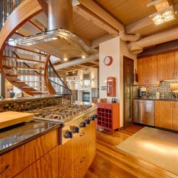 Kitchen with tiger wood floor and beige open ceiling; hardwood cupboards and cabinet; island with stove on left