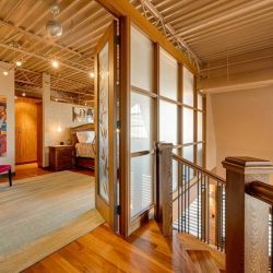 Interior entrance to loft bedroom with tiger wood floor, beige walls and open ceiling; glass doors open to bedroom on left; top of staircase on right