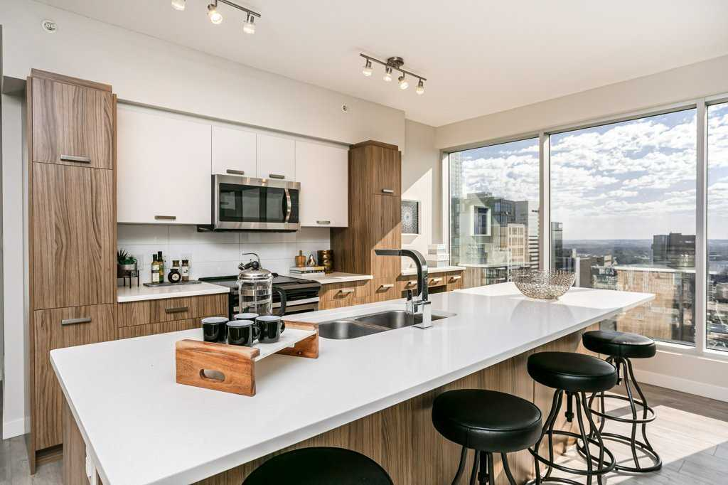 Interior condo kitchen with white marble island countertop with a sink, wood panel cupboards, light wood floor, four black stools; two-storey windows on right