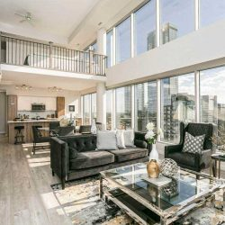 Interior condo living room, with dining and kitchen behind; black couch and chairs, glass coffee table on black-white-gold rug; two-storey windows with white pillars on the right; white wood staircase leading upstairs on left
